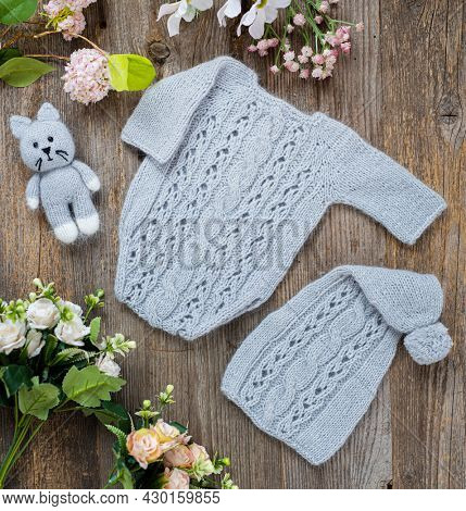 Knitted clothes composition for newborn on the wooden table. Infant woolen clothing design set with cute suit and hat light pink color