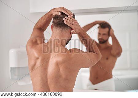 Sportive Man Strokes His Healthy Hair Looking In Large Mirror In Bathroom