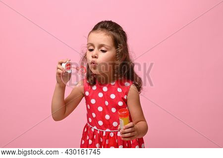 Cheerful Pretty Birthday Baby Girl In Stylish Pink Dress Blowing Soap Bubbles, Isolated Over Pink Ba
