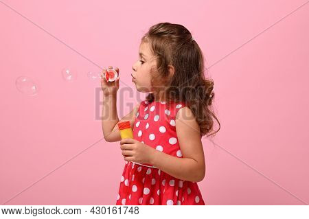 Side Portrait Of A Cheerful Beautiful Baby Girl Blowing Soap Bubbles, Isolated Over Pink Background