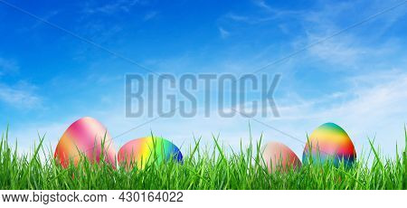 Group Of Pastel Colorful Easter Eggs On Green Grass With Blue Sky In Background.