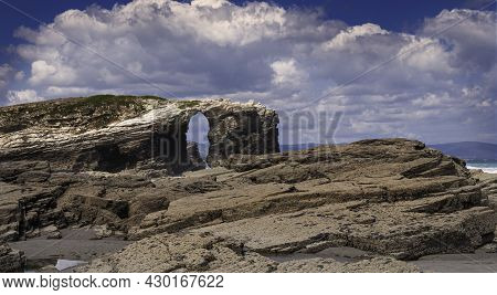 View Of Playa De Las Catedrales In Ribadeo, Galicia, With The Sea In The Background And Cloudy Sky.
