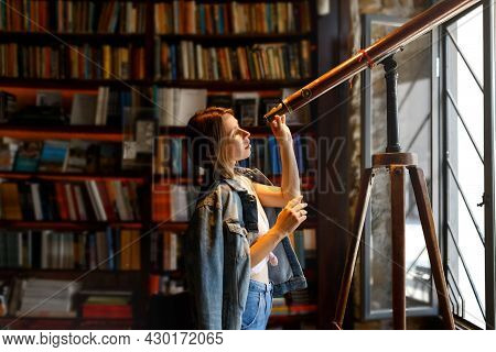 Young Hipster Female Looks Through A Telescope Standing In Vintage Library Room.