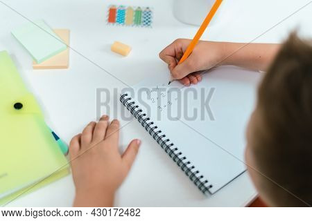 Distance Learning Online Education. Kid Boy Studying At Home With Book, Writing In Notepad And Doing