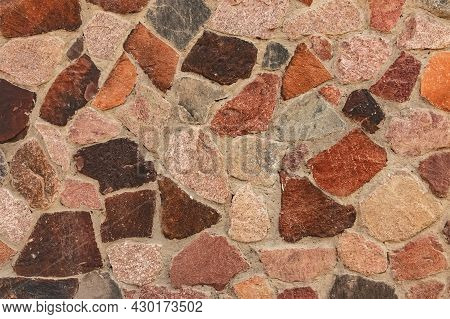 Decorative Wall Cladding With Large Granite Stones. Mosaic Background From Large Colored Natural Sto
