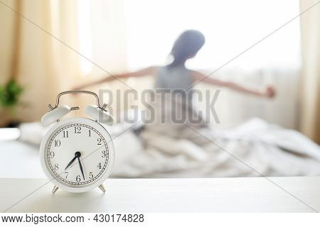 Little Boy Sitting And Stretching In Bed At Home In The Morning On A Window Background With Alarm Cl