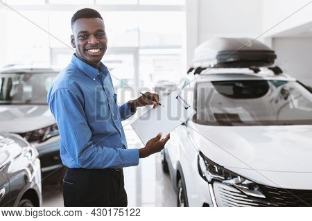 Cheerful Black Car Salesman Holding Empty Clipboard, Smiling At Camera In Modern Auto Dealership, Mo