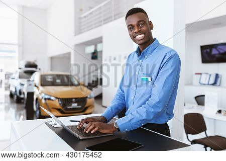 Cheerful Black Car Salesman Posing At Work Desk, Smiling At Camera, Typing On Laptop In Auto Dealers