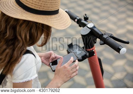 Electro-mobility. Traveler Unlocking An E-scooter On The Street. Traveler Exploring Old Town On Envi