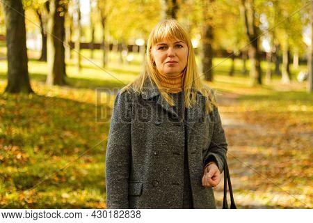 Defocus Serious Blond 40s Woman Posing In Yellow Autumn Park. Happy Beautiful Lady. Women Wearing Gr