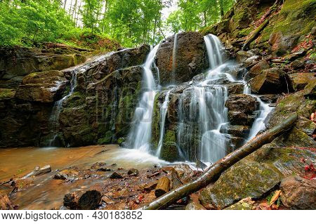 Landscape With Waterfall In Spring. Powerful Water Flow Comes Out Of The Rock