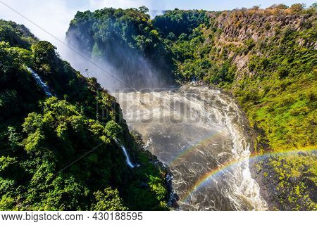 Grand and deep Victoria Falls after the wet season. Huge rainbow in the water mist over the Victoria Falls. Victoria Park, the Zambezi River. Concept of extreme and photo tourism