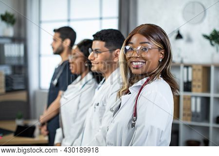 Smiling Pleasant Young African Female Doctor Standing In Light Hospital Room With A Diverse Multieth