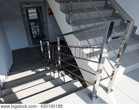 Modern Stairs With Metal Railing In Office Building. Staircase With Gray Floor Tiles. Emergency Exit