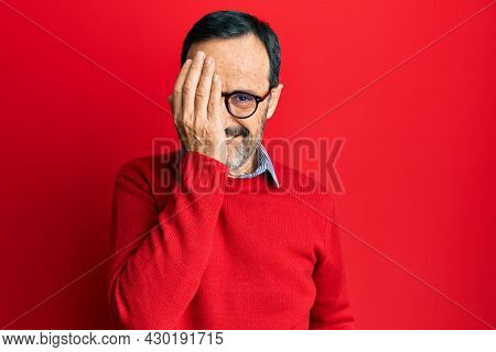 Middle age hispanic man wearing casual clothes and glasses covering one eye with hand, confident smile on face and surprise emotion.