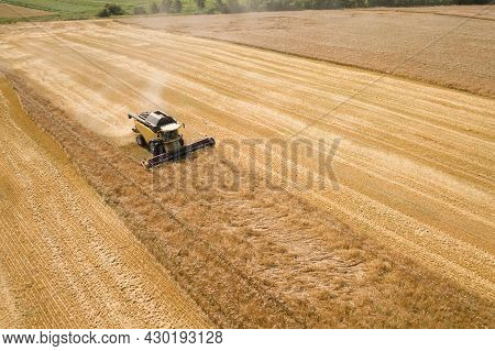 Aerial View Of Combine Harvester Harvesting Large Ripe Wheat Field. Agriculture From Drone View.