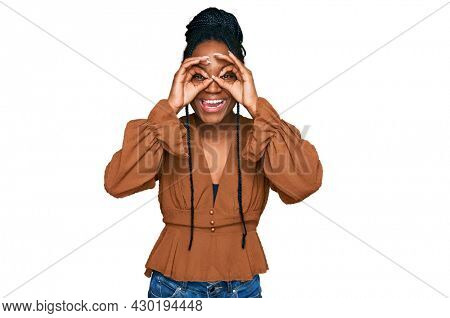 Young african american woman wearing casual clothes doing ok gesture like binoculars sticking tongue out, eyes looking through fingers. crazy expression.