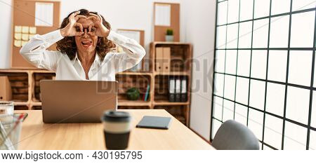 Middle age hispanic woman working at the office wearing glasses doing ok gesture like binoculars sticking tongue out, eyes looking through fingers. crazy expression.