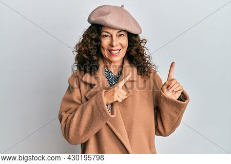 Middle age hispanic woman wearing french look with beret smiling and looking at the camera pointing with two hands and fingers to the side.