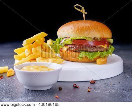 A Simple Hamburger On A White Plate. There Are French Fries And Yellow Sauce Nearby