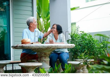 Asian Elderly Couple Happy Living At Home Sitting In The Garden In Front Of The House Laugh, Talk, H