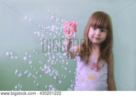 A Child Plays With Bubbles At Home. A Blurry Photo Of A Little Girl Playing With Soap Bubbles At Hom