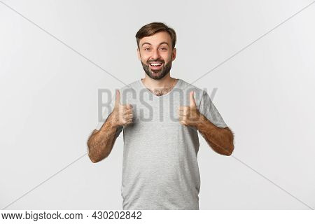 Image Of Handsome Bearded Man In Gray T-shirt, Looking Excited, Showing Thumbs-up In Approval, Like