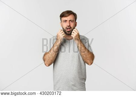 Portrait Of Horrified And Shocked Man Grimacing, Standing Anxious Over White Background