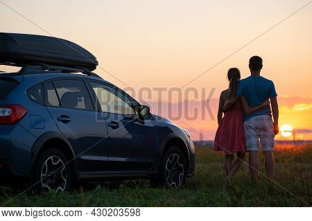 Happy Couple Relaxing Beside Their Suv Car During Honeymoon Road Trip At Sunset. Young Man And Woman