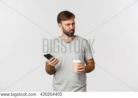 Image Of Confused Bearded Man Standing With Coffee And Mobile Phone, Looking Puzzled
