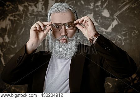 Funny senior man with a gray beard looks through glasses with big eyes and smiles. Vision and glasses concept.