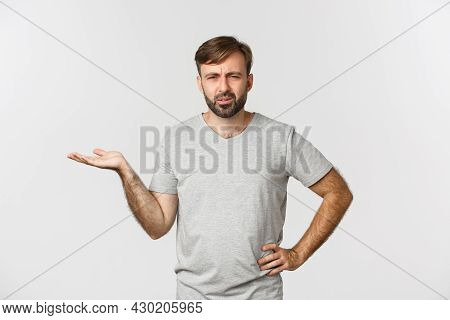 Portrait Of Confused And Annoyed Guy Arguing, Raising Hand Up And Looking Puzzled, Standing Over Whi