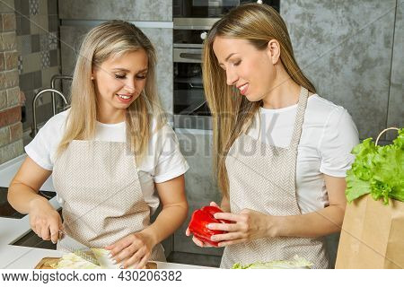 The Chef's Friends In Matching Kitchen Aprons Cook With Fresh Ingredients. Women Cooks Tenderly And