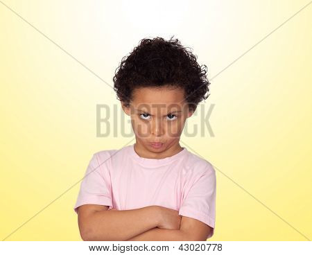 Angry latin child isolated on yellow background