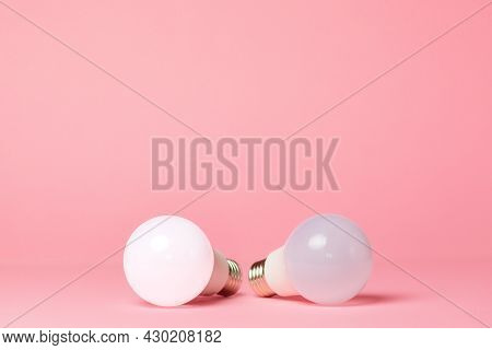 Breast Cancer Awareness Month. Two Electric Light Bulbs On A Pink Background. Close Up. Copy Space.