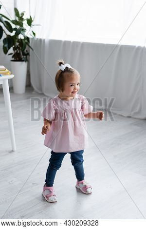 Disabled Kid With Down Syndrome Standing In Playroom