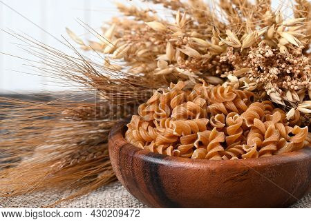 Bowl Of Wholegrain Pasta Spirals Or Fusilli, Over Light Wooden Background. Copy Space