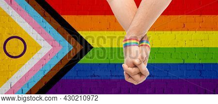 lgbtq, trans and intersex rights concept - close up of male couple hands with rainbow wristbands over progress pride flag on background