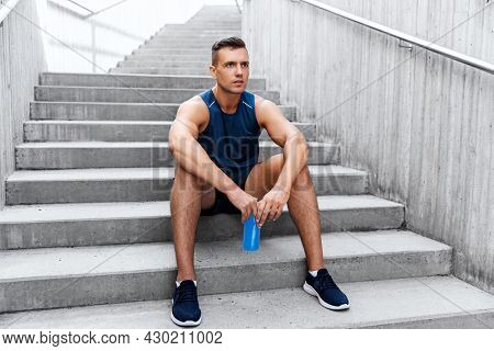 fitness, sport and people concept - tired young man with bottle of isotonic energy drink sitting on stairs