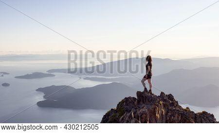 Adventurous Caucasian Woman Hiking On Top Of A Rocky Mountain Cliff. Sunny Summer Sunset. Mnt Brunsw