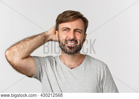 Close-up Of Puzzled Bearded Man, Looking Confused At Upper Left Corner, Scartching Head Indecisive,