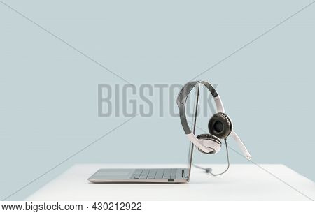 Side View Of Slim Laptop With Headphones Headset On White Desk. Blue Background. Distant Learning. W