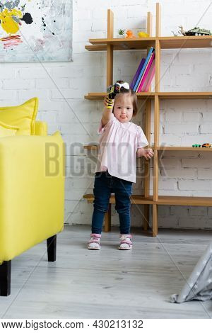 Kid With Down Syndrome Holding Toy Gun In Playroom