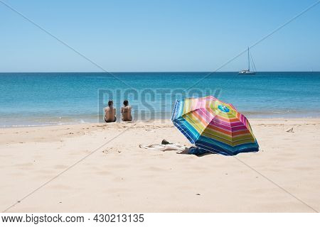 Adult Couple Sitting On A Beach Looking To The Sea. Seen From Their Back, Near To A Colorful Sun Umb