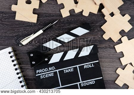 Cinematic  Clapper With Notepad, Pen And Puzzle Pieces On A Table Top View