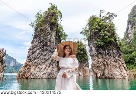 Happy Young Female Tourist In Dress And Hat At Longtail Boat Near Famous Three Rocks With Limestone