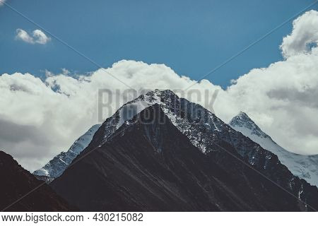 Atmospheric Mountain Landscape With Great Snow-covered Pinnacle And Snowy Pointy Peak In Low Clouds