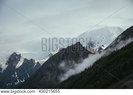 Scenic Alpine Landscape With Great Snowy Mountain And Low Cloud On Mountainside With Forest. Atmosph
