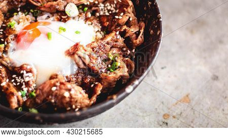 Korean Pork With Egg On Rice In Bowl Ceramic Plate With Metal Spoon And Fork. A Traditional Korean T