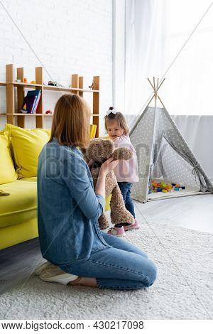 Kindergarten Teacher Holding Teddy Bear Near Child With Down Syndrome In Playroom
